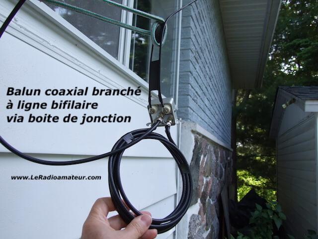 Boite de jonction reliant une ligne d'alimentation bifilaire et un câble coaxial servant à protéger les connexions des intempéries. Vue de la boite installée à l'extérieur.
